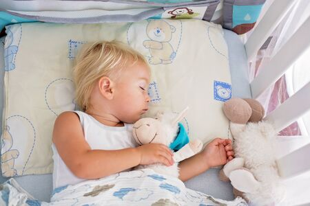 Sweet baby boy in casual clothes, sleeping in bed with teddy bear stuffed toys, summertime Standard-Bild