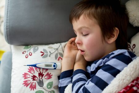 Sick little child, boy, with high fever sleeping on the couch at home, lots of medicine on the table Stock fotó