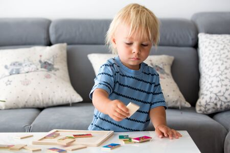 Little toddler doing puzzle. Boy learning basic developing cognitive skills, child concept