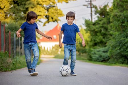 Two cute little kids, playing football together, summertime. Children playing soccer outdoor Archivio Fotografico - 129406840