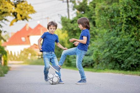 Two cute little kids, playing football together, summertime. Children playing soccer outdoor Archivio Fotografico - 129406450