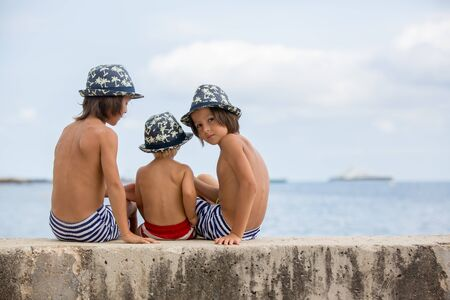 Three children, boy brothers, sitting on a concrete wall on pier on the sea, contemplating the boats in the water, hugging and smiling