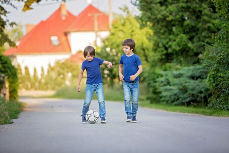Two cute little kids, playing football together, summertime. Children playing soccer outdoor Archivio Fotografico - 129406486