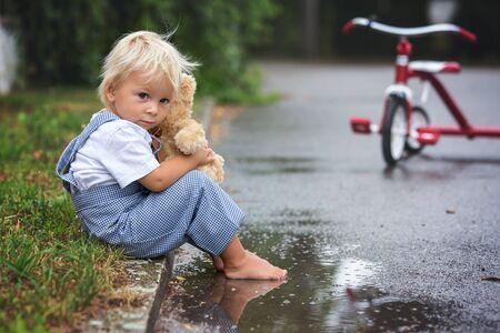 Süßer kleiner Junge, mit Teddybär-Spielzeug, im Regen auf der Straße sitzend, barfuß, sein Dreirad auf einer Seite Standard-Bild