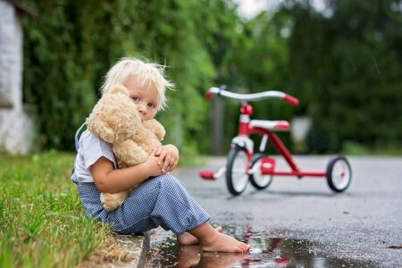 Cute little boy, with teddy bear toy, sitting on the street in the rain, barefeet, his tricycle on a side