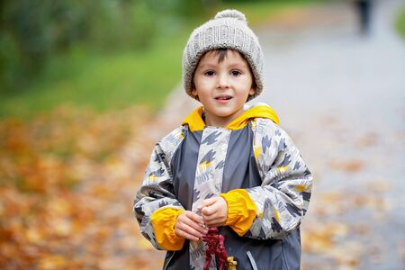 Sweet child, boy, playing in the park on a rainy day, autumn time