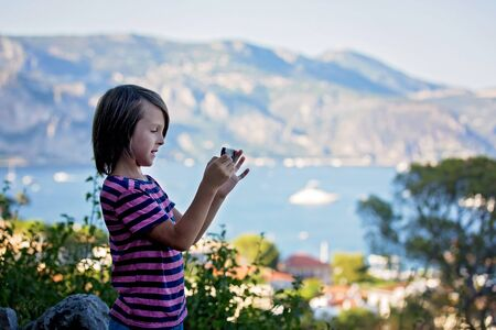 Preteen child, taking pictires with mobile of view on French Riviera from top 写真素材