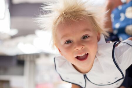 Funny two years old child, boy, hanging upside down, smiling happily, mom holding him Stock Photo