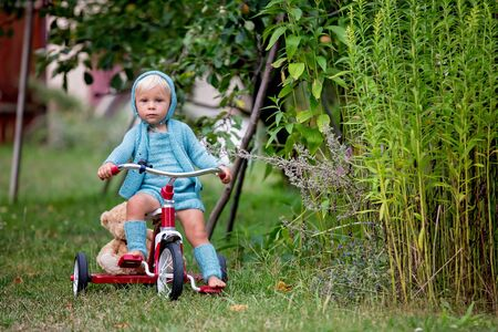 Adorable toddler boy with knitted outfit, riding tricycle on a quiet village street, summertime Stock Photo