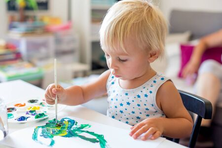 Little toddler boy, painting at home, learning coordination of moves and colors
