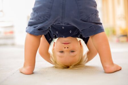 Child standing upside down, smiling happily while having fun