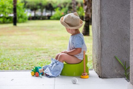 Sweet toddler boy, sitting on potty on a back porch in a holiday resort patio, playing with toys Stock Photo