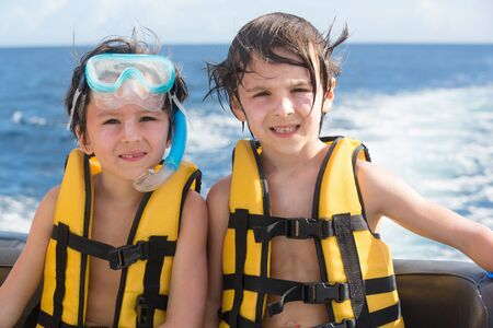 Happy family with life vests, having fun on a boat trip while on holiday in Mauritius 스톡 콘텐츠