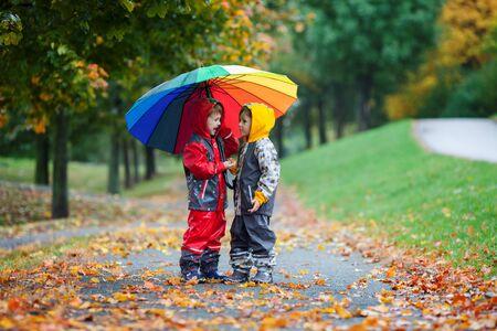 Dwoje uroczych dzieci, bracia, bawią się w parku z kolorowym tęczowym parasolem w deszczowy jesienny dzień