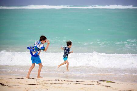 Adorabili bambini in età prescolare, ragazzi, che si divertono sulla spiaggia dell'oceano. Bambini emozionati che giocano con le onde, nuotano, sguazzano allegramente, si godono le vacanze in famiglia a Mauritius