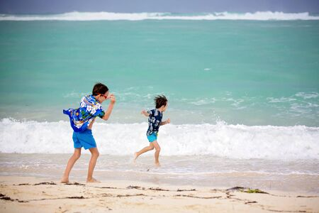 Adorable preschool children, boys, having fun on ocean beach. Excited children playing with waves, swimming, splashing happily, enjoying family vacation in Mauritius