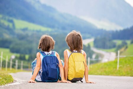 Little children, boy brothers with backpacks and sutcase, travel on the road to scenic mountains