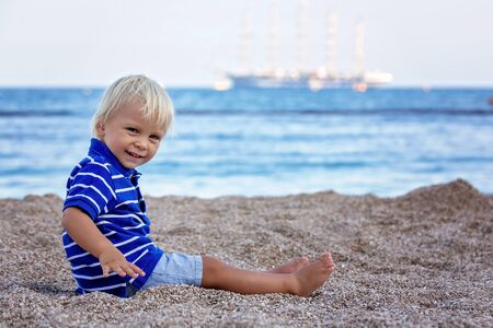 Toddler child, sitting on beach, watching lighted ship in the ocean on sunset