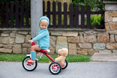 Adorable toddler boy with knitted outfit, riding tricycle on a quiet village street, summertime Stok Fotoğraf