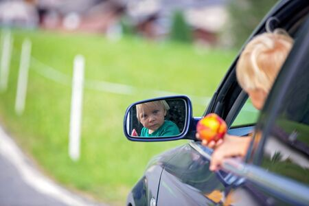 Cute child, boy looking from a car window, travel on the road to scenic mountains, summertime