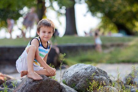Cute child, boy, sitting on a lake coast, evening portrait, summertime