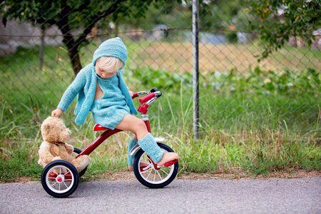 Entzückender Kleinkindjunge mit Strickoutfit, der im Sommer Dreirad auf einer ruhigen Dorfstraße fährt