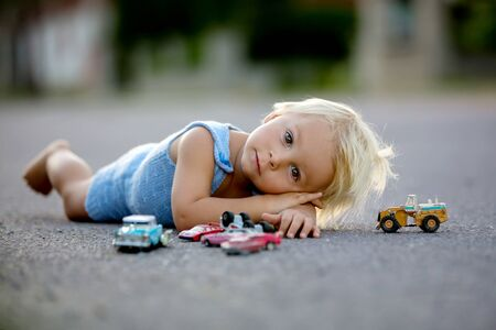 Beautiful child, playing with car toys on sunset on a quiet village street, summertime