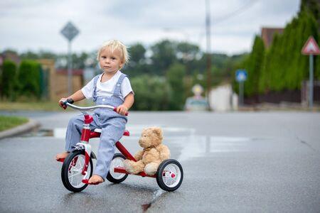 Netter kleiner Junge, mit Teddybär-Spielzeug, Dreirad auf der Straße im Regen fahren, barfuß, Sommer