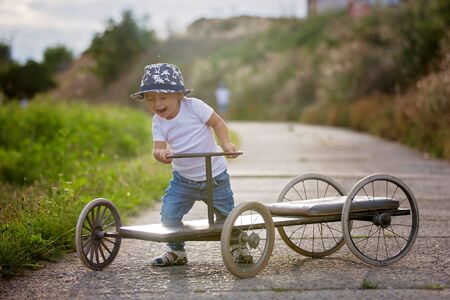 Adorable toddler boy, riding old retro car with four wheels in a village 스톡 콘텐츠