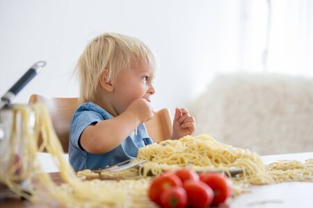 Little baby boy, toddler child, eating spaghetti for lunch and making a mess at home, pot with spaghetti and tomatoes on the table 写真素材