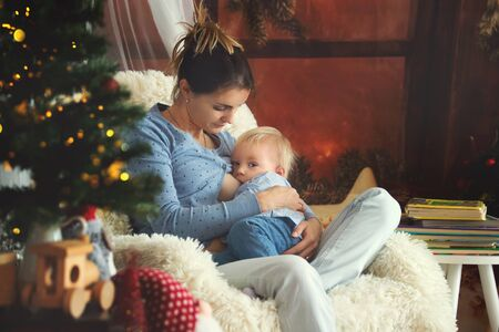 Mother breastfeeding her toddler son sitting in cozy armchair near Christmas tree, wintertime 免版税图像 - 130068769