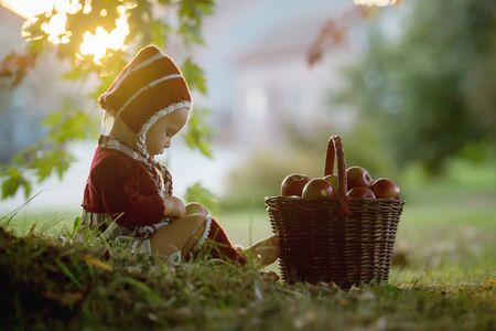 Child eating apples in a village in autumn. Little baby boy playing with apples. Kids pick fruit in a basket. Toddler eating fruits at fall harvest. Outdoor fun for children