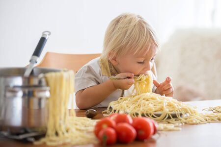 Little baby boy, toddler child, eating spaghetti for lunch and making a mess at home, pot with spaghetti and tomatoes on the table Stock Photo