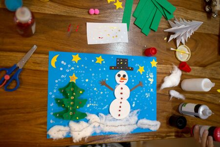 Top view of child, doing snowman and winter tree. Scissors, glue stick, pencil, markers, paper sheets and scraps on wooden background. Fun children winter background