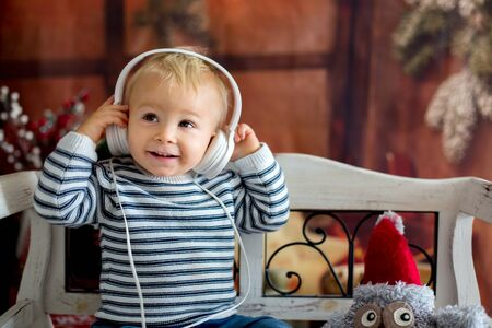 Sweet toddler boy with headphones, listening to music, sitting on rustic bench, christmas decoration behind him. Childhood, kids, technology and Christmas concept