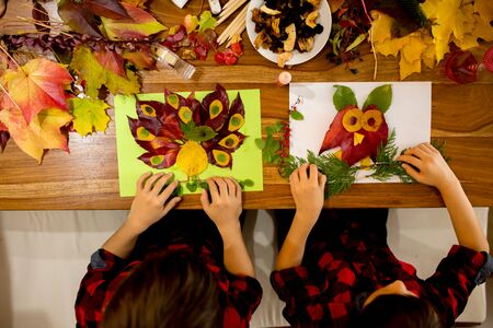 Children, applying leaves using glue, scissors, and paint, while doing arts and crafts in school, autumntime Stock Photo