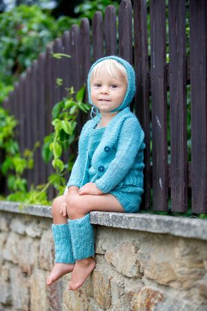 Beautiful portrait of toddler boy with handmade knitted outfit and teddy bear, sitting on a stone wall, hugging his toy