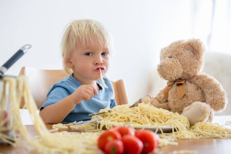 Little baby boy, toddler child, eating spaghetti for lunch and making feeding teddy bear friend, pot with spaghetti and tomatoes on the table