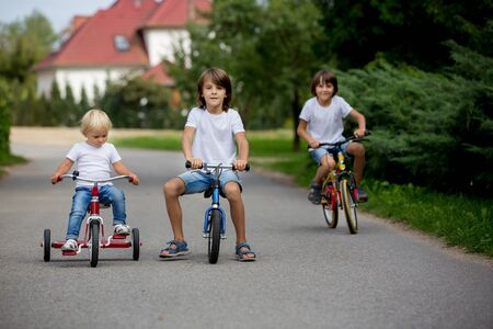 Three children, brothers, riding bike, tricycle and balance bike on the street in quiet village, happily competing