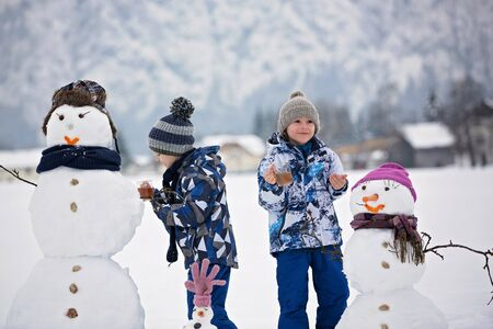 Family with children, building snowman in the park in little village in Austria, beuatiful landscape scenery