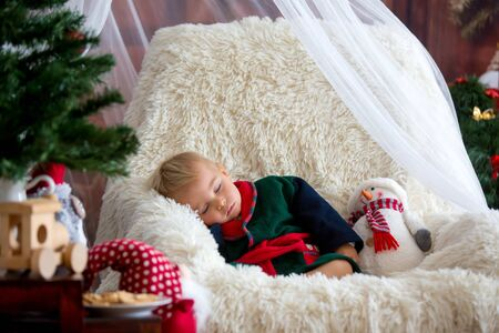 Baby boy, cute child, wearing santa claus robe sitting in rocking chair with Christmas tree and lights on background in room, sleeping, eating cookies. Merry Christmas. Holiday season.