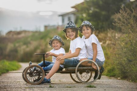 Happy children, boy brothers, riding old retro car with four wheels in a village 스톡 콘텐츠 - 130068926