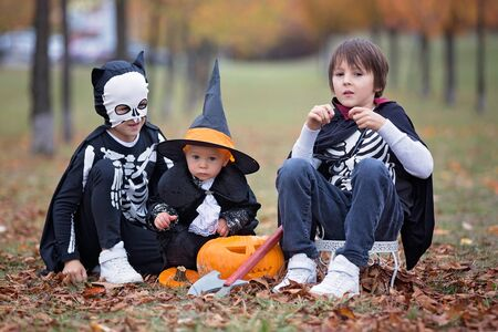 Children having fun with halloween carved pumpkin in a park, wearing scary costumes and playing with toys