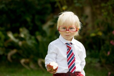 Cute kid, wearing glasses and eating apple, dressed for first day of school or kindergarden, happy smiling