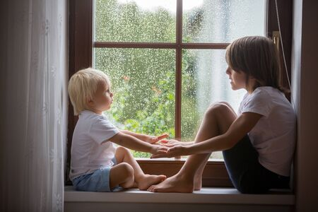 Happy siblings, boy brothers, sitting on a window shield on a rainy day, playing together, summertime Stock fotó