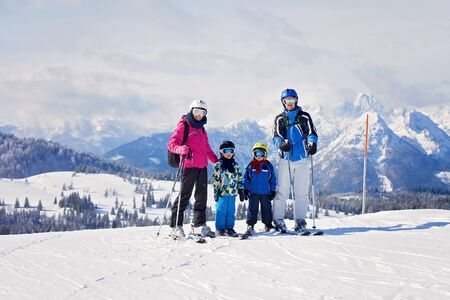 Young happy family with two childrens, boy brothers, skiing in Austrian ski resort on a sunny winter day