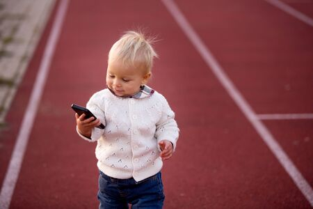 Fashionable little toddler boy with knitted outfit, walking in autumn park with phone in hands