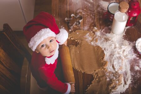 Sweet toddler child, boy, helping mommy preparing Christmas cookies at home in kitchen Фото со стока