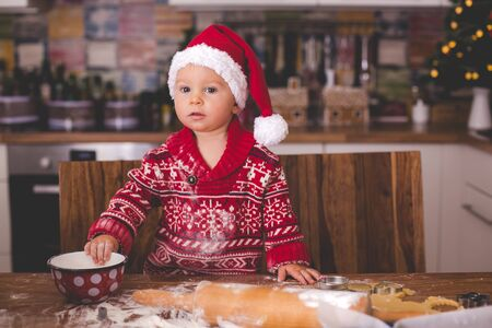 Sweet toddler child and his older brother, boys, helping mommy preparing Christmas cookies at home in kitchen