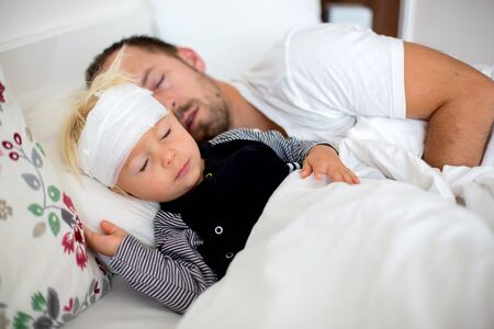 Little toddler boy with head injury, lying with dad in bed, tired, sleeping Imagens